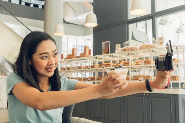 De gelukkige vrouw neemt selfie met haar cake in het koffie.