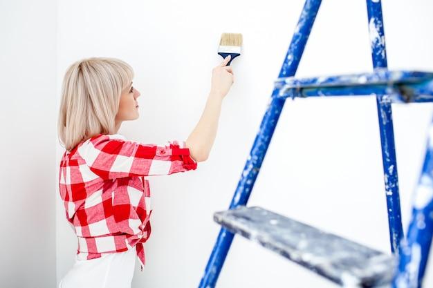 De gelukkige vrouw schildert muur met rol thuis