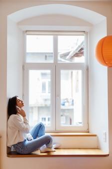 De gelukkige vrouw spreekt op telefoon terwijl het zitten dichtbij het venster