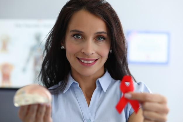 De gelukkige vrouw toont borstimplantaat en rood lint