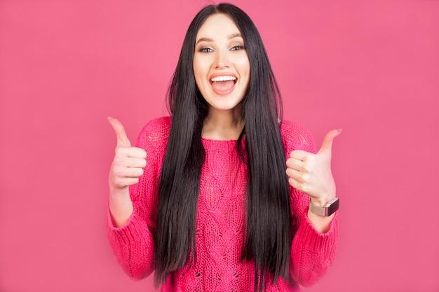 De gelukkige vrouw toont duimen, aan beide handen, breed glimlachend, een emotie van geluk, op een roze achtergrond. het concept van goedkeuring en geluk door te krijgen wat je hebt gekocht.