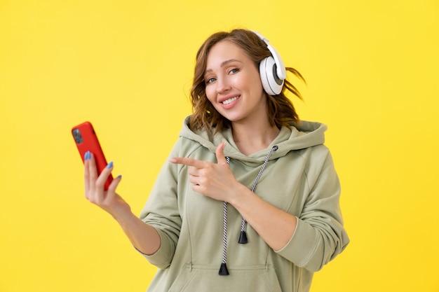 De gelukkige vrouw van de tandenglimlach luistert muziekhoofdtelefoons die smartphone in de hand houden