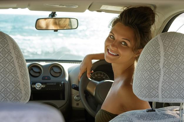 De gelukkige vrouwelijke bestuurder zit in de auto