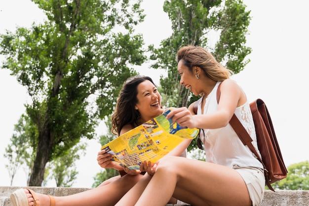 De gelukkige vrouwelijke kaart die van de toeristenholding ter beschikking elkaar bekijken