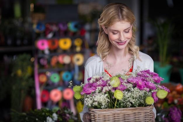 De gelukkige vrouwelijke mand van de bloemistholding van bloemen