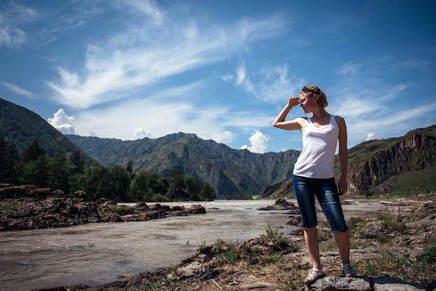 De gelukkige vrouwelijke toerist in een wit t-shirt en denimborrels bevindt zich op bank van bergrivier op zonnige dag.