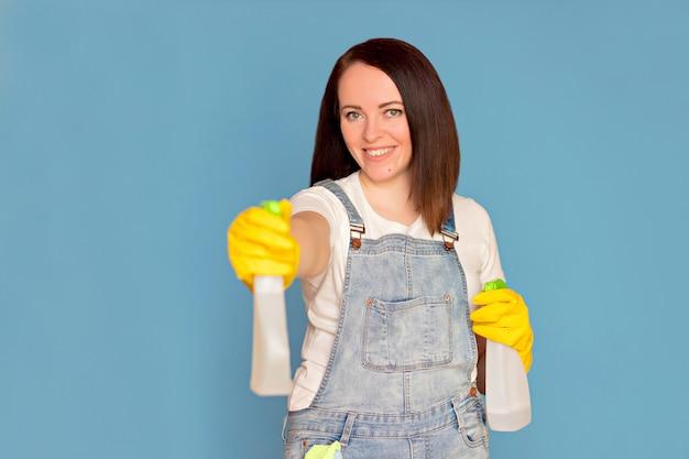 De gelukkige vrouwen schoonmaakster in rubberhandschoenen houdt een detergens in haar handen. zuiverheid concept