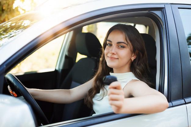 De gelukkige vrouwenbestuurder opschept over het ontvangen van rijbewijs die autosleutel tonen en gelukkig en in hoge geest voelen. jonge student meisje heeft haar eerste auto