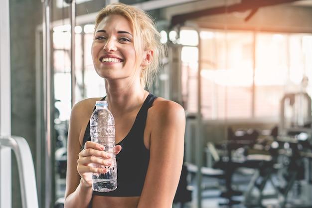 De gelukkige welzijnsvrouw drinkt water na training in gymnastiek.