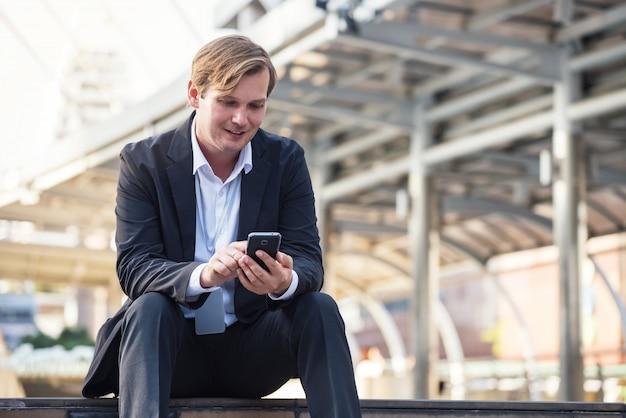 De gelukkige werknemer gebruikt smartphone in stad