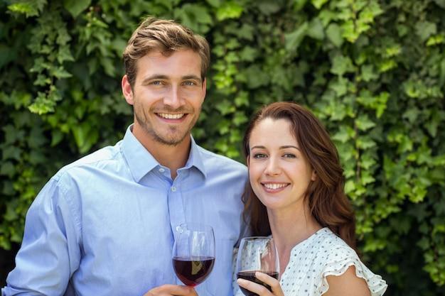 De gelukkige wijnglazen van de paarholding bij voortuin