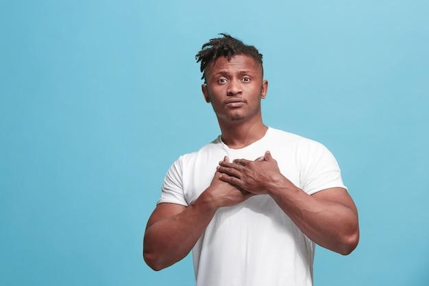 De gelukkige zaken afro-amerikaanse man staan en glimlachen tegen een blauwe achtergrond.