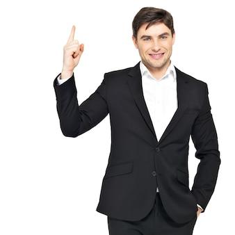 De gelukkige zakenman benadrukt zijn vinger in zwart kostuum dat op wit wordt geïsoleerd