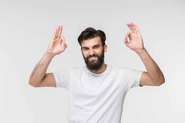 De gelukkige zakenman die en zich tegen witte muur bevindt glimlacht