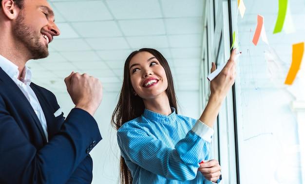 De gelukkige zakenman en een zakenvrouw die op het kantoorglas tekenen