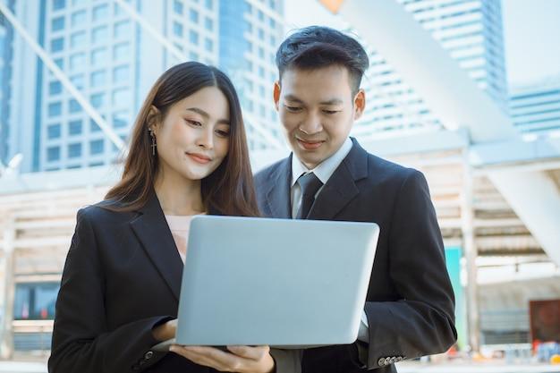 De gelukkige zakenman en onderneemsterhanden houden laptop buiten.