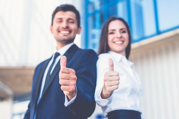 De gelukkige zakenman en vrouw duimen omhoog