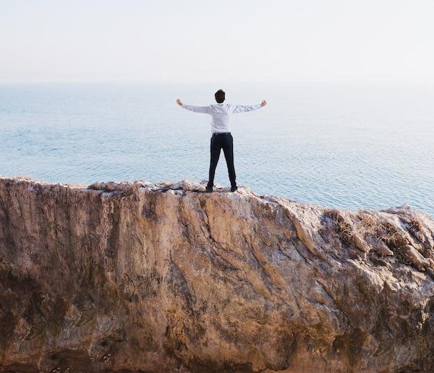 De gelukkige zakenman juicht voor zijn zakelijk succes over een hoge berg