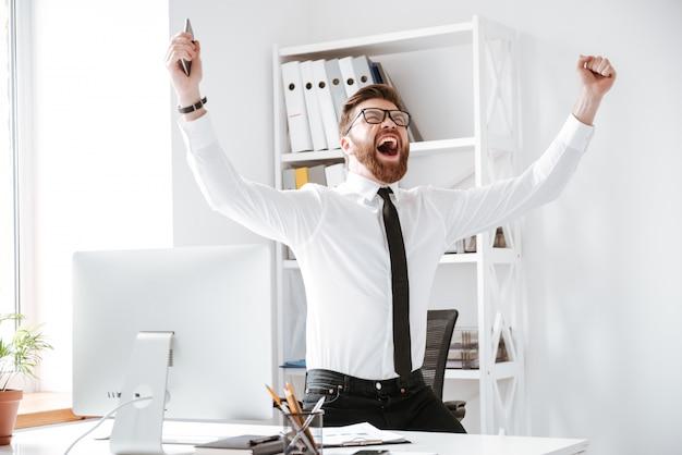 De gelukkige zakenman maakt winnaargebaar.