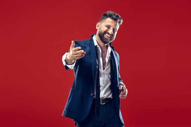 De gelukkige zakenman staat en lacht tegen de rode muur