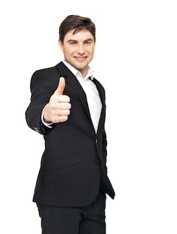 De gelukkige zakenman toont duimen omhoog teken in zwart kostuum dat op wit wordt geïsoleerd.