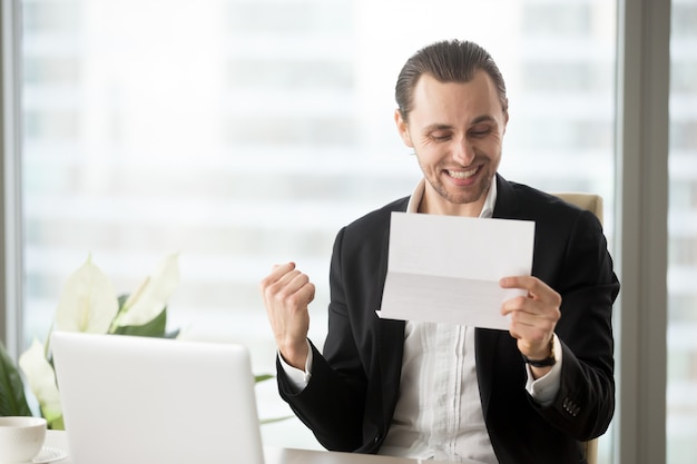 De gelukkige zakenman viert ontvangend goed bedrijfsnieuws