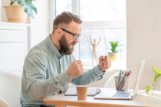 De gelukkige zakenman voelt opwinding, heft vuisten op, bekijkt laptop goed nieuws ontvangt, levensdoelen bereikt, bedrijfssucces viert, maakt een winnaargebaar. concept van succes en doel bereiken.