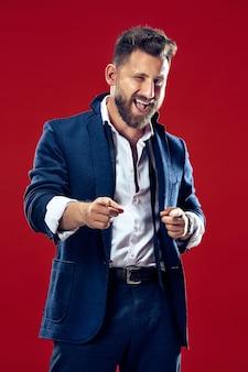 De gelukkige zakenman wijst je en wil je een close-upportret van de halve lengte op de rode muur