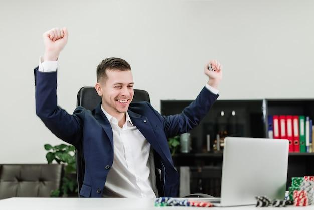 De gelukkige zakenman wint in online casino terwijl het spelen van poker in het kantoor op het werk
