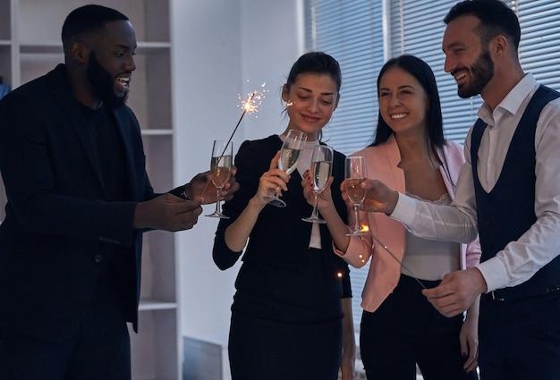 De gelukkige zakenmensen die champagne drinken en sterretjes vasthouden
