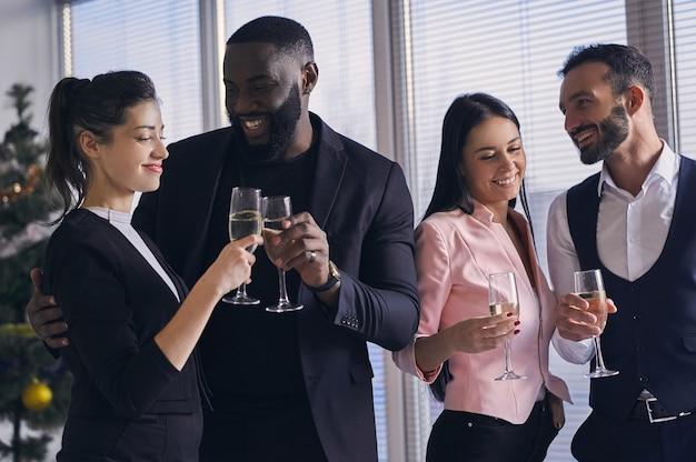 De gelukkige zakenmensen die champagne drinken op kantoor