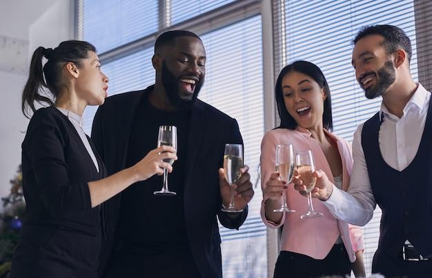 De gelukkige zakenmensen die champagne drinken
