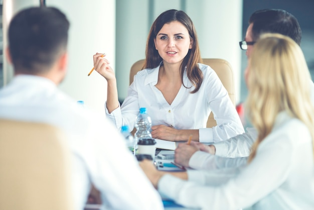 De gelukkige zakenmensen zitten aan tafel en praten