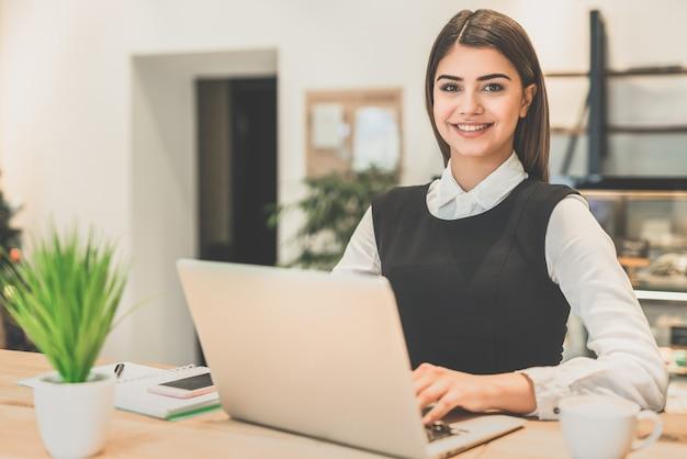 De gelukkige zakenvrouw die met een laptop werkt