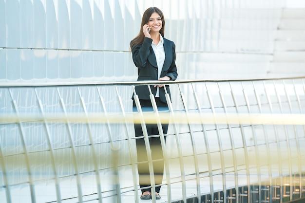 De gelukkige zakenvrouwentelefoon op het kantoorbalkon