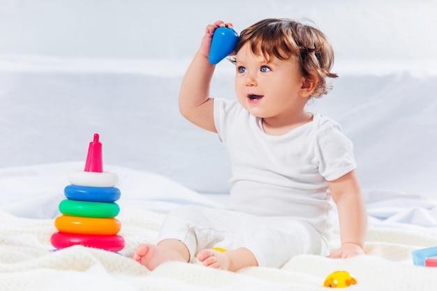 De gelukkige zitting van de babyjongen met stuk speelgoed