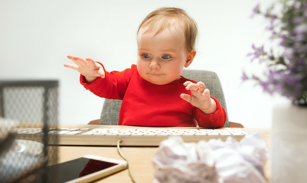 De gelukkige zitting van de het meisjespeuter van de kindbaby met geïsoleerd toetsenbord van computer