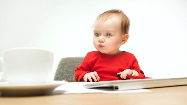 De gelukkige zitting van de het meisjespeuter van de kindbaby met toetsenbord van computer die op een wit wordt geïsoleerd