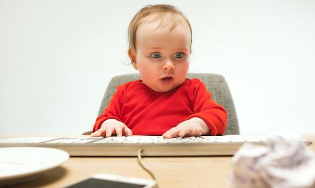 De gelukkige zitting van de het meisjespeuter van de kindbaby met toetsenbord van computer die op een witte achtergrond wordt geïsoleerd