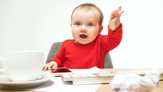 De gelukkige zitting van de het meisjespeuter van de kindbaby met toetsenbord van de computer die op een wit wordt geïsoleerd