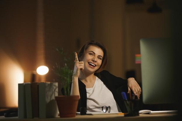 De gelukkige zitting van de jonge dameontwerper in bureau bij nacht