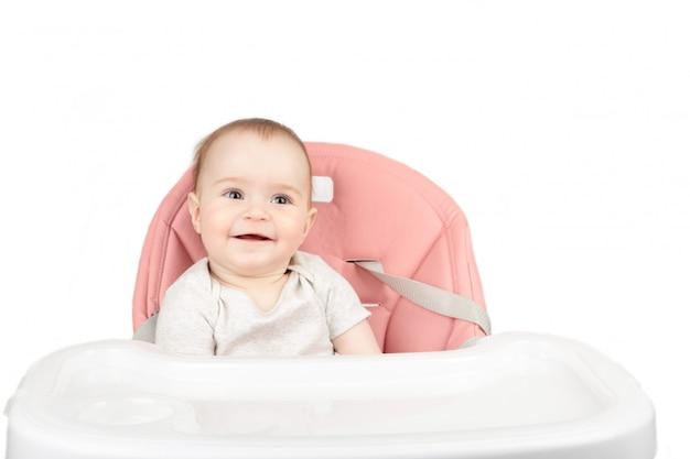 De gelukkige zitting van het babymeisje als hoge voorzitter en glimlach die op witte achtergrond wordt geïsoleerd
