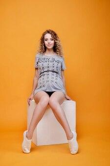 De gelukkige zwangere jonge mooie vrouw van het manier blonde model in studiozitting op witte kubus op geeloranje smilles