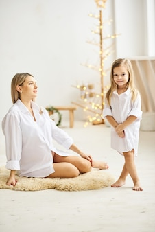 De gelukkige zwangere moeder en haar dochter koesteren elkaar