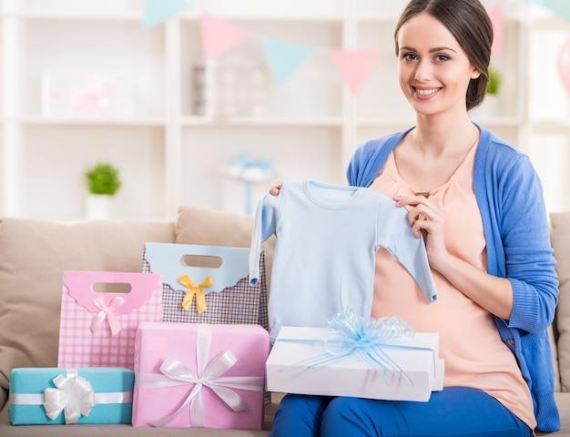 De gelukkige zwangere vrouw zit met stelt voor.