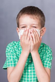 De gemaskerde jongen houdt hoesten vast en bedekt zijn mond met zijn handen.