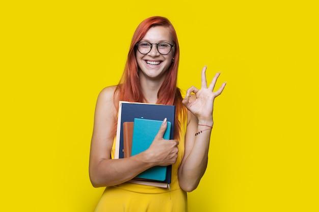 De gember sproeten student gebaart het ok teken op een gele studiomuur met boeken en draagt een jurk en een bril