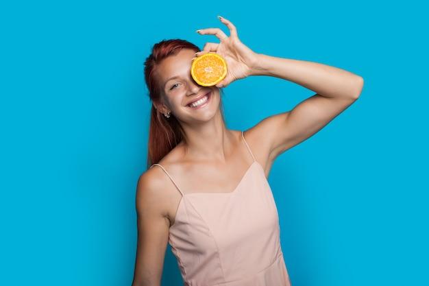 De gembervrouw glimlacht terwijl ze haar oog bedekt met een sinaasappel die zich voordeed op een blauwe muur
