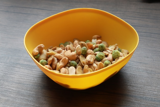 De gemengde droge pindacachou en de noten in de gele kom zetten op houten lijst achtergrondsnackvoedsel voor vegetariër