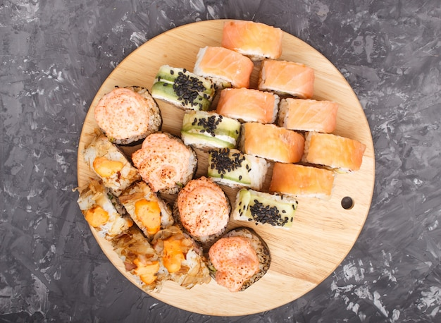 De gemengde japanse die broodjes van makisushi op zwarte concrete achtergrond, hoogste mening worden geplaatst.